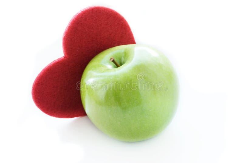 Maçã verde com coração vermelho imagens de stock royalty free