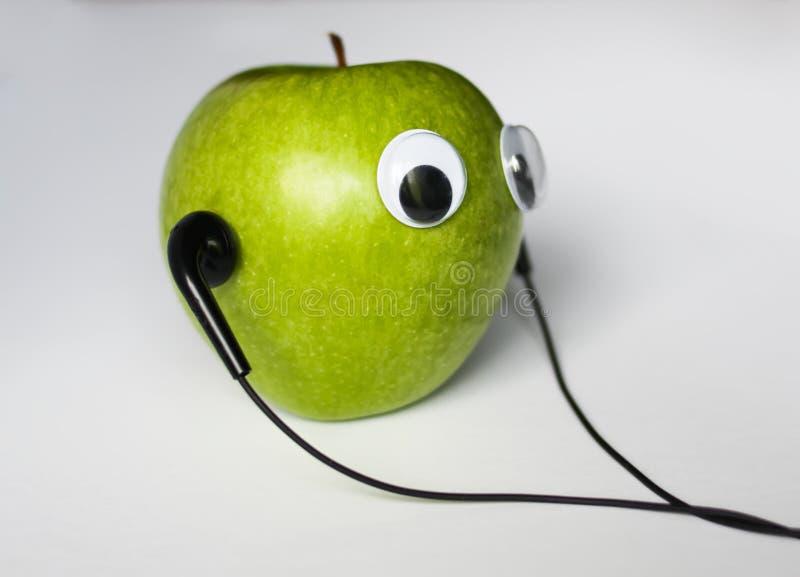 Maçã verde com olhos bonitos e fones de ouvido no fundo branco Foto conceptual fotos de stock royalty free