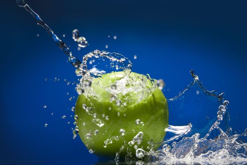 Maçã verde com respingo da água no azul imagem de stock