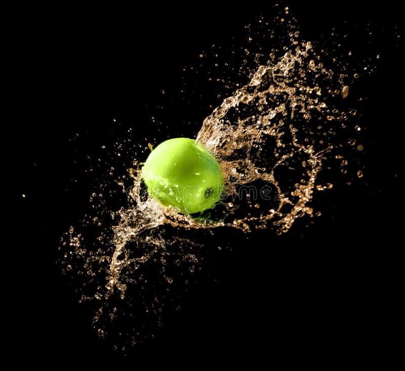 Maçã verde com respingo da água, no preto imagens de stock