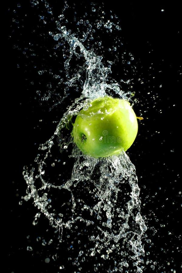 Maçã verde com respingo da água, no preto fotografia de stock royalty free