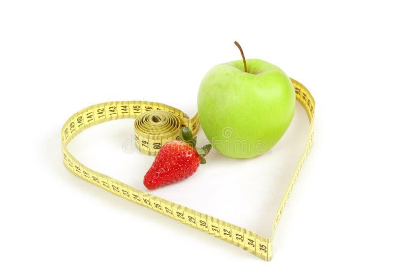 Maçã verde com um símbolo de medição da fita e do coração isolada imagens de stock