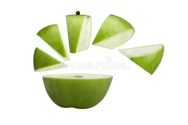Maçã verde cortada em partes e em fatias. imagem de stock