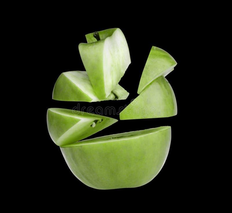 Maçã verde cortada em partes e em fatias. foto de stock