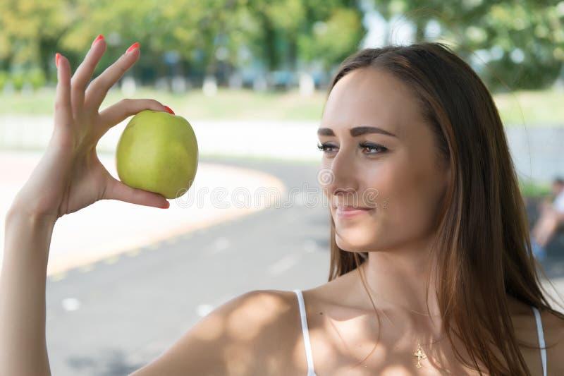 Maçã verde das posses adoráveis e saudáveis da mulher O segredo de sua beleza é nutrição saudável Dieta ou apoio da menina imagem de stock royalty free