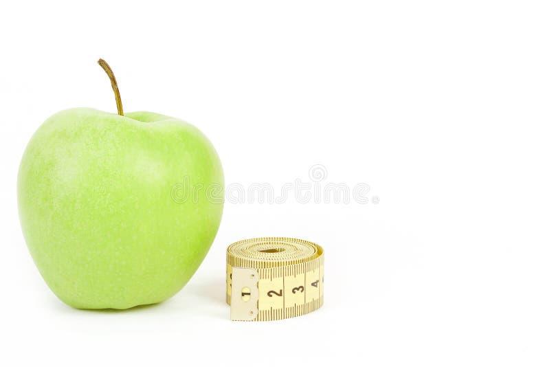 Maçã verde e fita de medição isoladas no fundo branco fotografia de stock