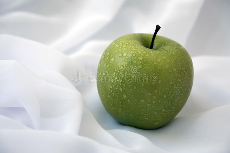 Maçã verde em um fundo branco, com gotas de água foto de stock