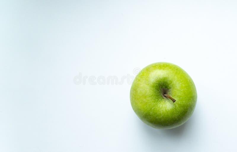 Maçã verde em um lugar branco do fundo para uma inscrição fotografia de stock royalty free