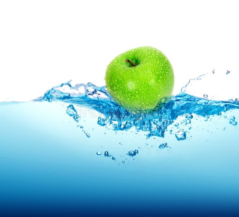 maçã verde fresca no respingo da água azul com bolhas no CCB branco fotografia de stock royalty free