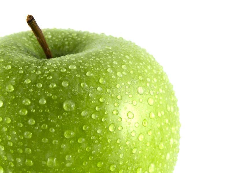 A maçã verde isolada com água deixa cair no branco foto de stock