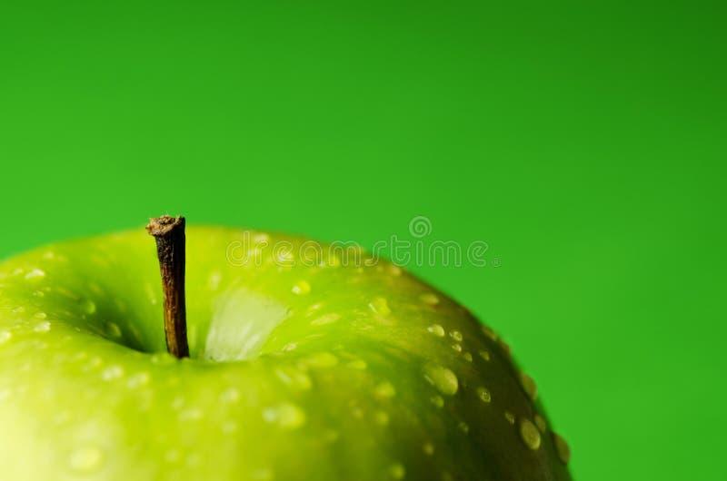 A maçã verde madura com água deixa cair no fundo imagem de stock royalty free