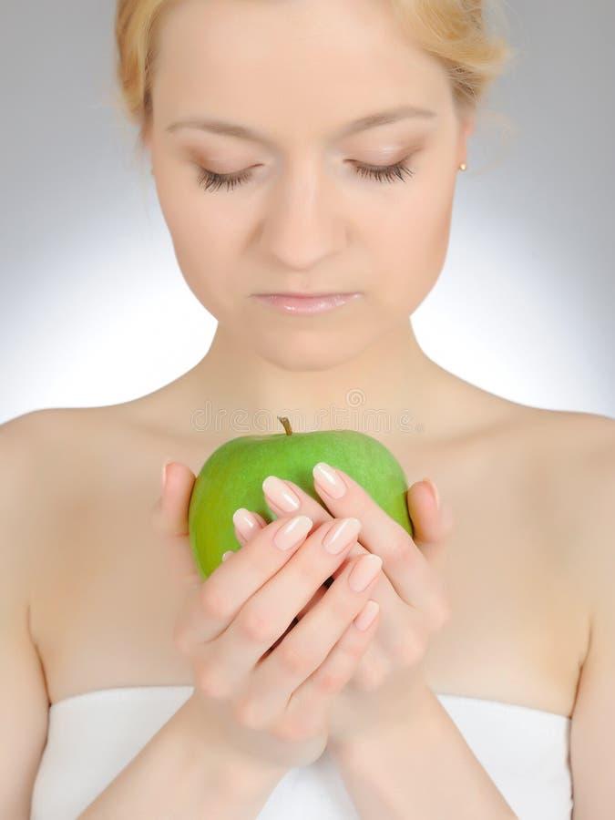 Maçã verde na mão manicured bonita da mulher imagens de stock
