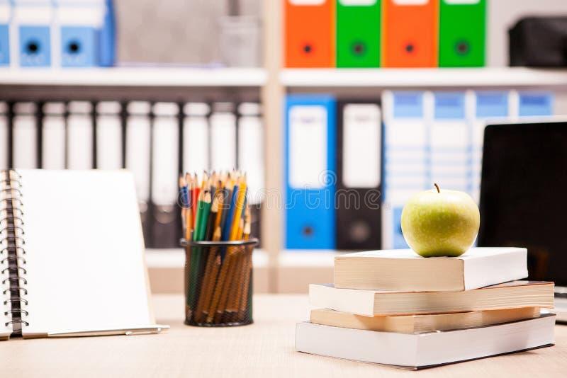 Maçã verde na pilha dos livros ao lado de um caderno e dos lápis em t fotografia de stock royalty free