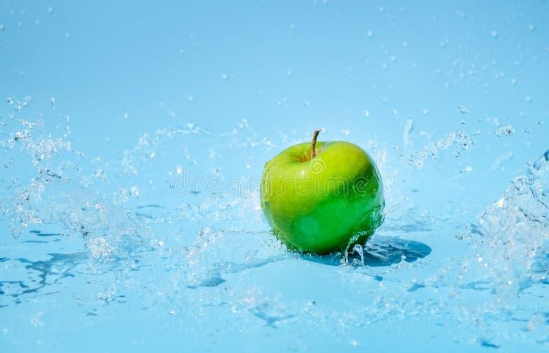 Maçã verde no respingo claro da água imagens de stock royalty free
