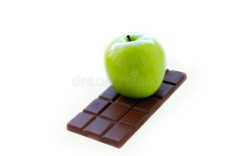 Maçã verde que encontra-se na barra de chocolate imagem de stock royalty free