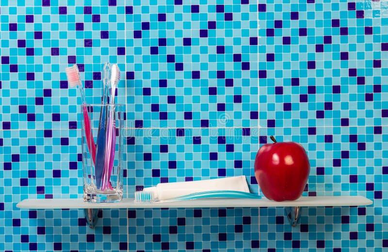Maçã vermelha com dentífrico e escova na prateleira fotografia de stock royalty free