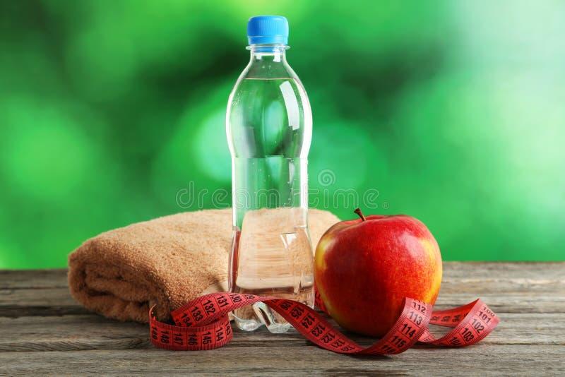 Maçã vermelha com fita e a garrafa de medição da água no fundo de madeira cinzento imagens de stock