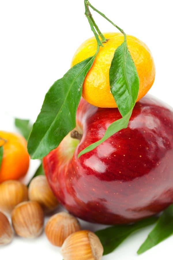 Maçã vermelha, mandarino com folhas do verde e porcas fotos de stock royalty free