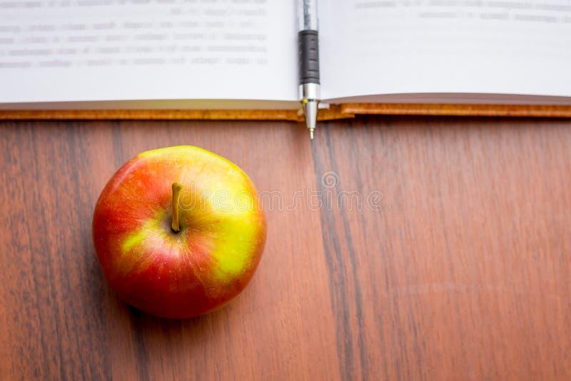 Maçã vermelha suculenta madura perto do livro e da pena Alimento útil durante a fotos de stock royalty free