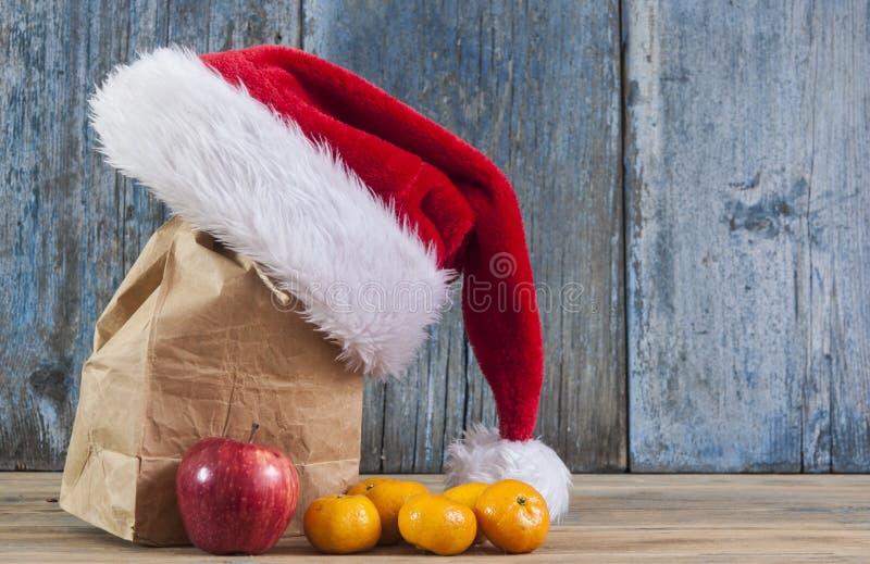 maçã vermelha, tangerina madura e chapéu de Santa Claus no backgrou de madeira foto de stock royalty free