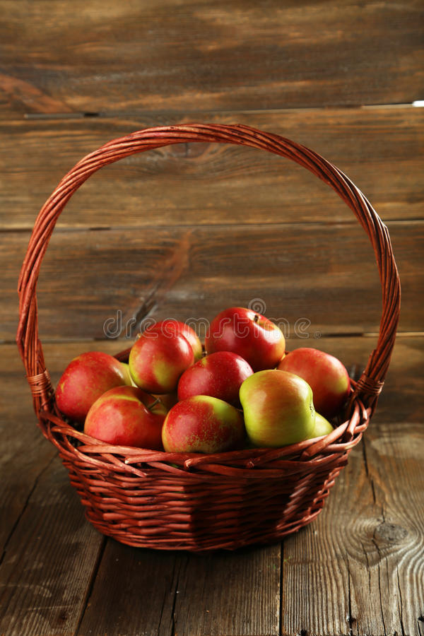 Maçãs bonitas na cesta no fundo de madeira marrom foto de stock