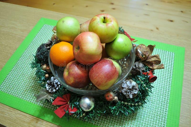Maçãs coloridas do outono em uma cesta decorada com decorações do Natal fotografia de stock
