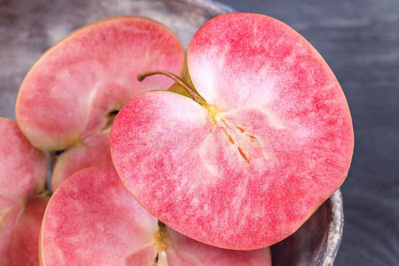 Maçãs com carne cor-de-rosa em um fundo escuro fotografia de stock royalty free