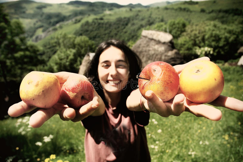 Maçãs de sorriso da terra arrendada da menina fotos de stock royalty free