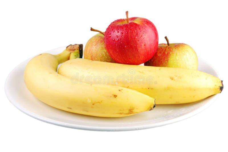 Maçãs e bananas frescas em uma placa branca com fundo branco imagem de stock