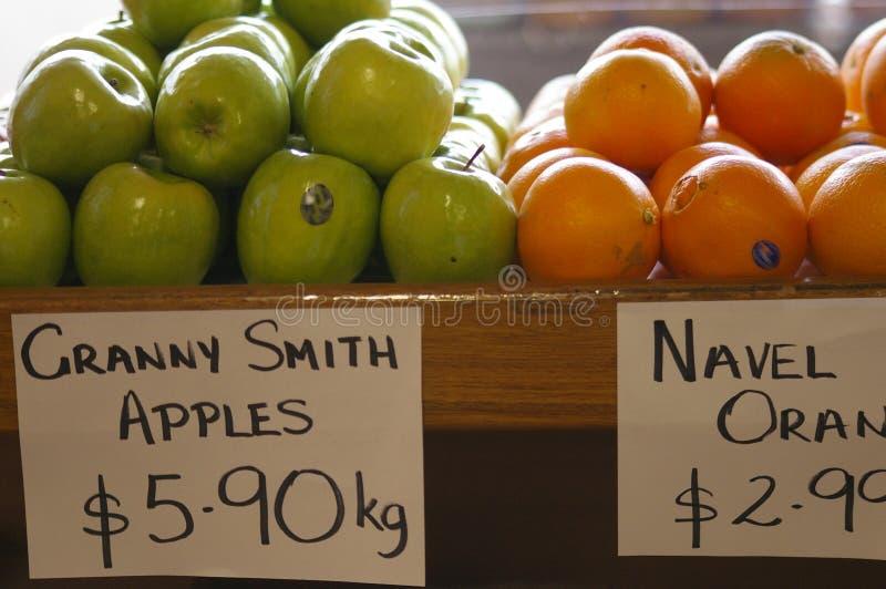 Maçãs e laranjas que estão sendo vendidas em um quitandeiro verde local foto de stock