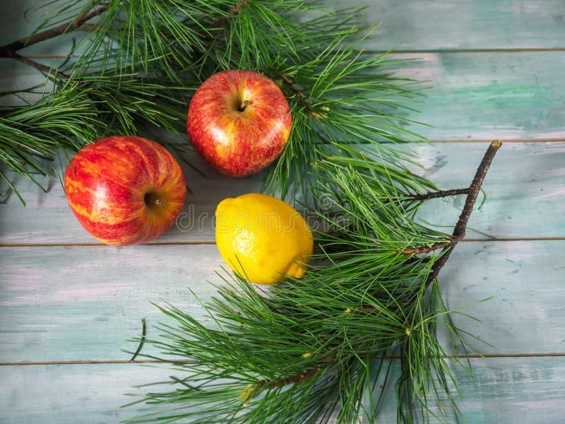 Maçãs e limão entre os ramos do abeto em um fundo de madeira foto de stock