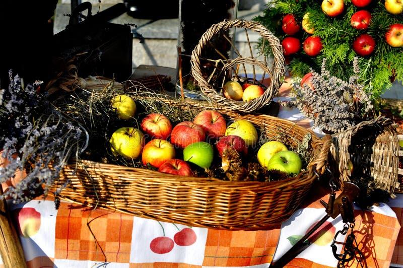 Maçãs e porcas coloridas em uma cesta de madeira em uma tabela com vida de cultivo retro velha do outono dos objetos ainda foto de stock