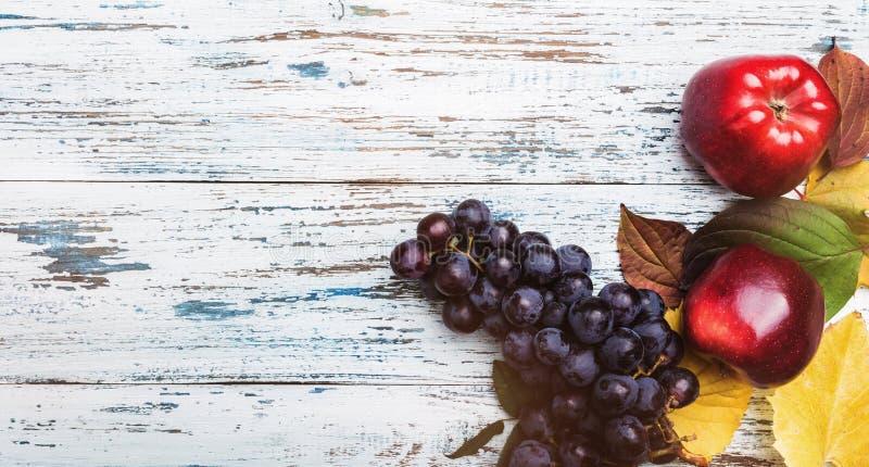 Maçãs e uvas em um fundo rústico de madeira A ideia superior do outono frutifica, foco seletivo fotografia de stock royalty free