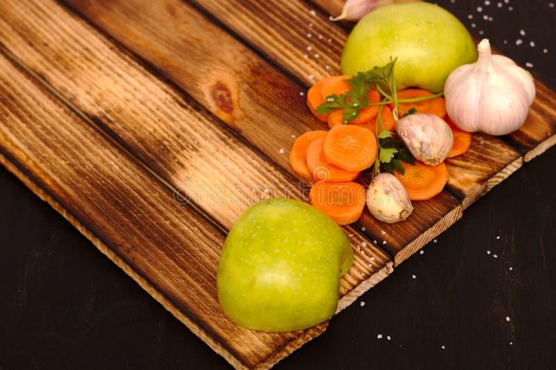 Maçãs e vegetais em uma placa de madeira fotografia de stock royalty free