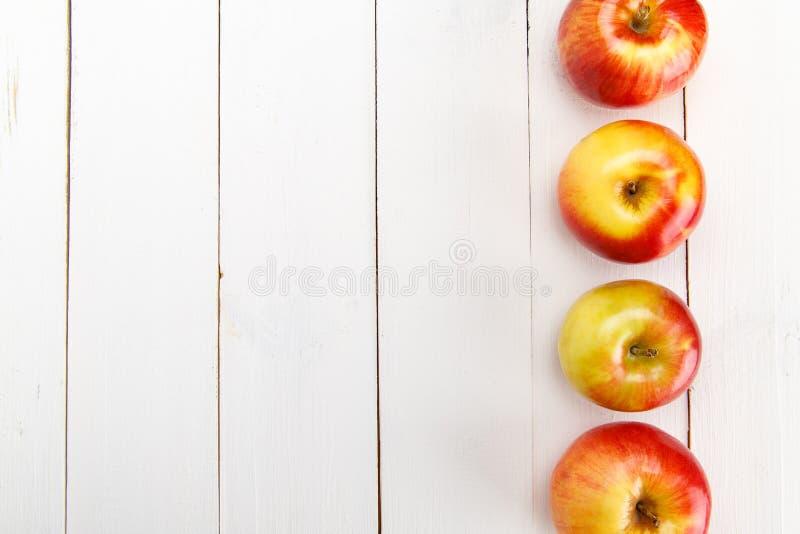 Maçãs frescas em uma tabela de madeira branca imagens de stock