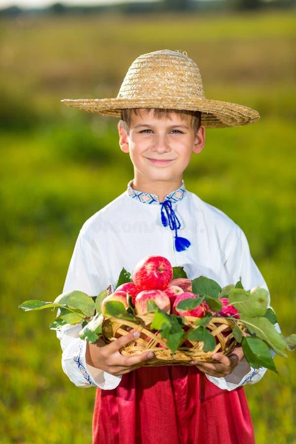 Maçãs orgânicas da posse feliz do menino do fazendeiro em Autumn Garden fotografia de stock royalty free
