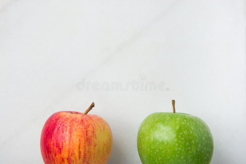Maçãs orgânicas vermelhas verdes maduras no fundo de mármore branco Abaixe a beira Imagem minimalista criativa para o Web site cu fotos de stock