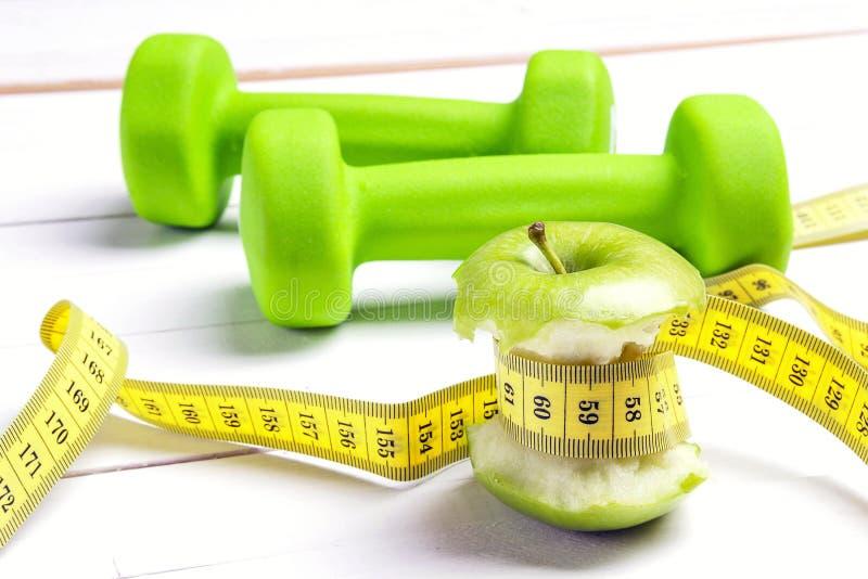 Maçãs verdes com a fita de medição com pesos verdes em w branco fotografia de stock