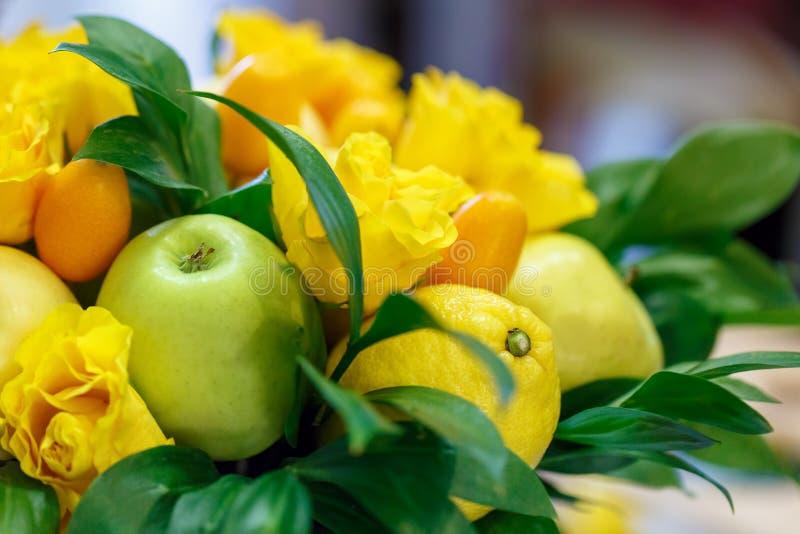 Maçãs verdes, limão amarelo, kumquat e rosas amarelas sob a forma do ramalhete feito a mão foto de stock