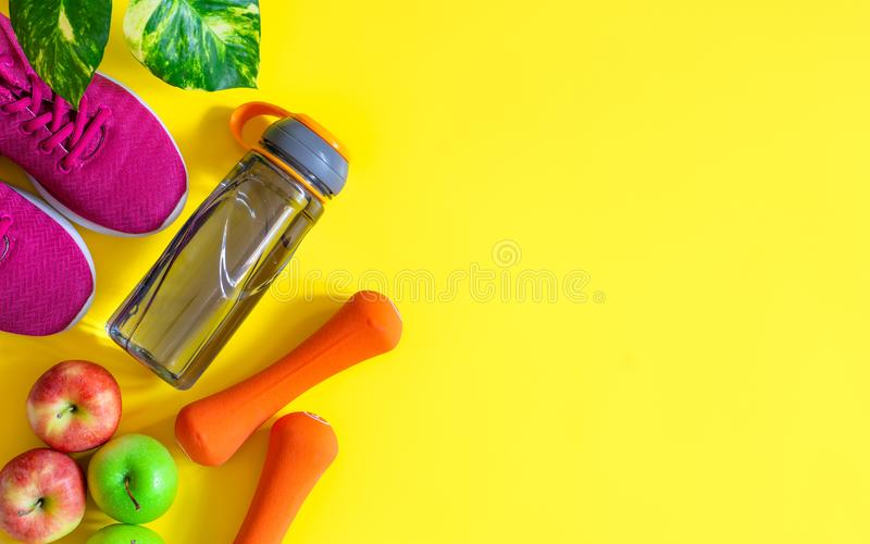 Maçãs vermelhas e verdes, garrafa da água, pesos alaranjados e sapatas vermelhas do esporte no fundo amarelo Estilo de vida saudá imagem de stock