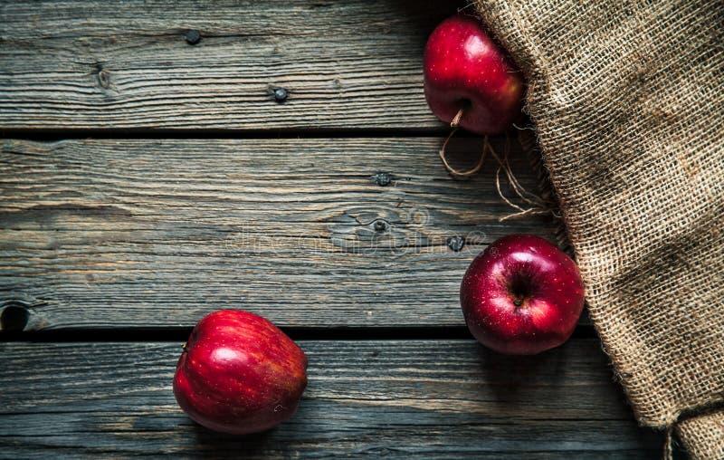 Maçãs vermelhas em um fundo de madeira com despedida fruto, alimento natural imagem de stock royalty free