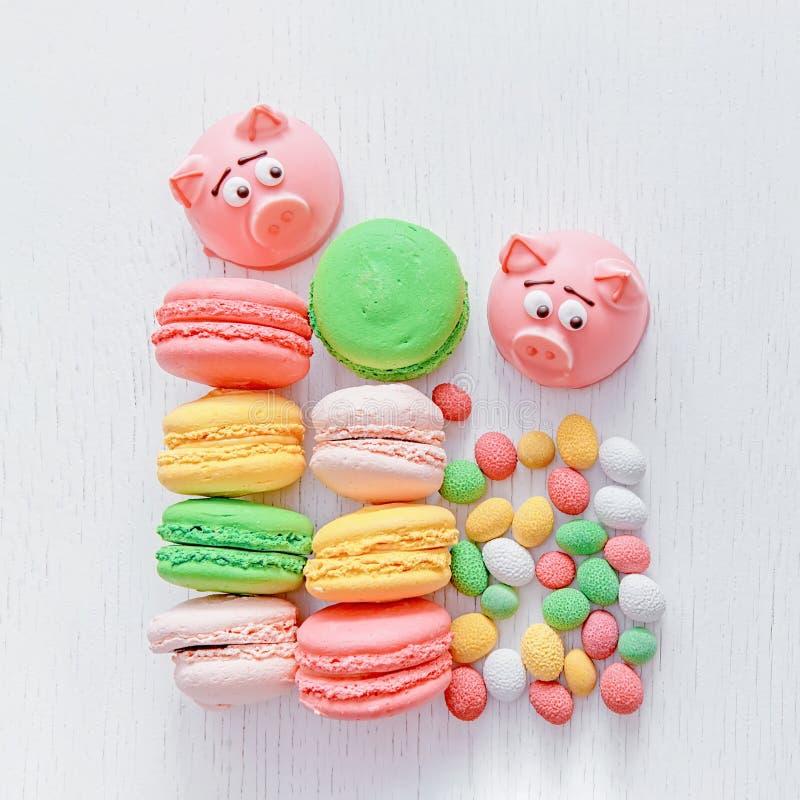 Maçapão na forma do símbolo do ano novo - porco cor-de-rosa, bolinhos de amêndoa delicados doces, marshmallows, amendoins no açúc imagens de stock royalty free