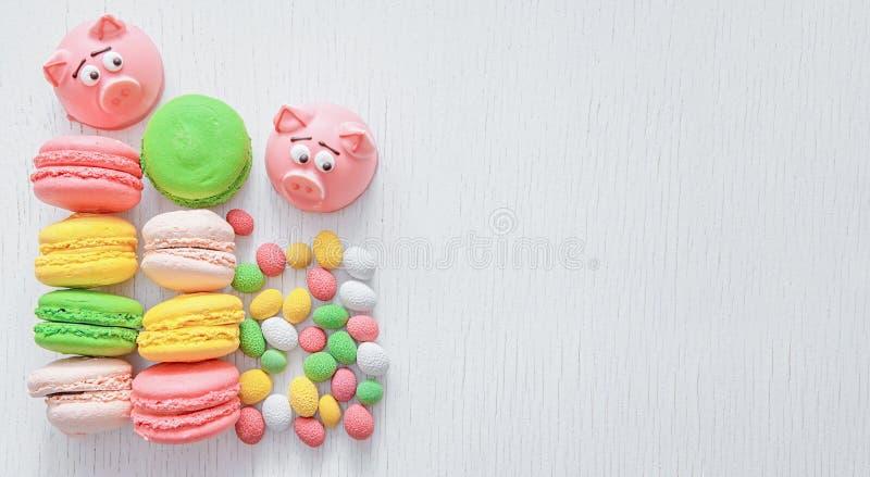 Maçapão na forma do símbolo do ano novo - porco cor-de-rosa, bolinhos de amêndoa delicados doces, marshmallows, amendoins no açúc fotografia de stock royalty free