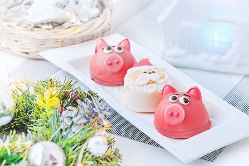 Maçapão na forma do símbolo do rosa do ano novo - porco, bolinhos de amêndoa delicados doces, marshmallows, amendoins na cor past imagem de stock