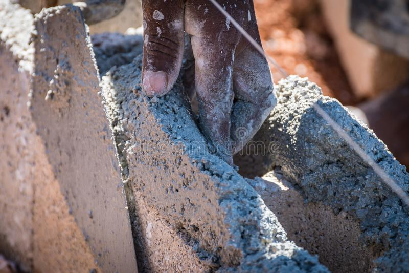 Maçon/maçon appliquant le ciment humide sur des blocs de béton images libres de droits