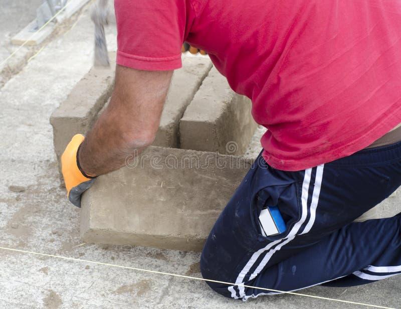 Maçon travaillant avec des briques de boue pour construire un mur image stock