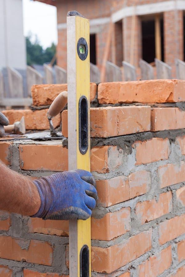 Maçon Using un niveau de bâtiment pour vérifier le nouveau mur de briques rouge extérieur Techniques de maçonnerie de fondements  image stock