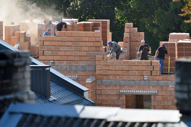 Maçons installant la maçonnerie de brique image libre de droits