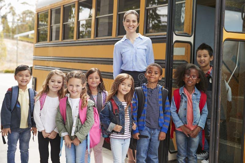 Maître d'école élémentaire et élèves se tenant prêt l'autobus scolaire image libre de droits