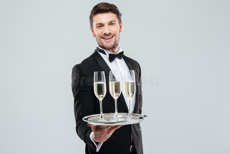 Maître d'hôtel gai en champagne de sourire et de offre de smoking images libres de droits
